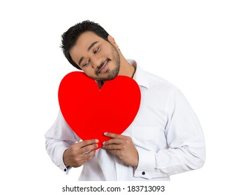 Closeup portrait happy smiling handsome man looking upwards, holding large red heart to chest daydreaming of women in love, isolated white background. Positive emotion facial expression feelings