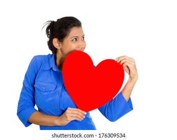 Closeup portrait of happy smiling pretty woman looking upwards, holding large red heart to chest daydreaming of men in love, isolated on white background. Positive emotion facial expression feelings