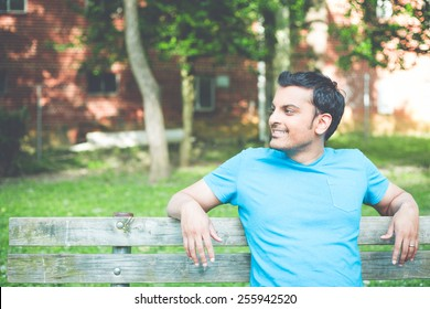 Closeup portrait, happy smiling, regular young man in blue shirt sitting on wooden bench, relaxed looking to side, isolate background trees, woods. Retro faded vintage look