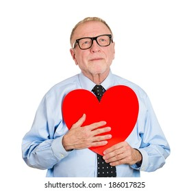 Closeup portrait, happy smiling, senior mature man looking upwards, holding large red heart to chest daydreaming of women in love, isolated white background. Positive emotion facial expression feeling