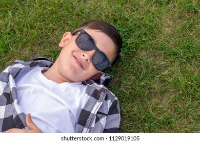 Close-up portrait of happy smiling well-dressed teenager having rest on green grass in trendy sunglasses. Summer time weekend mood. Copy space in right side
