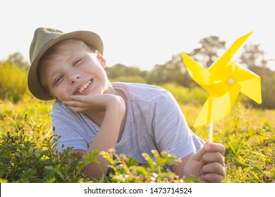 Closeup portrait of happy smiling white kid relaxing happily in sunny sunset meadow outside. Boy holding yellow plastic pinwheel toy in hand. Horizontal color photography.