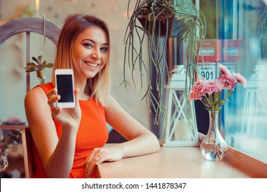 Closeup portrait happy smiling woman holding a smartphone showing blank black screen in her home kitchen, near window or in a coffee shop, trendy cafe wearing red dress. Look here at my phone concept.