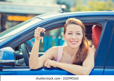 Closeup portrait happy, smiling, young attractive woman, buyer sitting in her new blue car showing keys isolated outside dealer, dealership lot office. Personal transportation, auto purchase concept