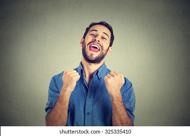 Closeup portrait happy successful student, business man winning, fists pumped celebrating success isolated grey wall background. Positive human emotion facial expression. Life perception, achievement