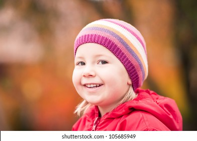 Closeup portrait of a happy toddler girl on autumn day