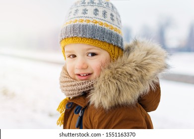 Closeup portrait of happy two year old toddler boy outdoors on snowy winter day, smiling, wearing knitted hat, scarf and jacket with furry cap. Natural lighting, mild retouch.