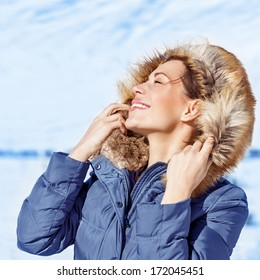 Closeup portrait of happy woman with closed eyes enjoying sun light in cold frosty day, wearing fashionable wintertime clothes, luxury model in snowy park