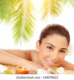 Closeup portrait of happy woman lying down on massage table on tropical beach in sunny day, enjoying day spa, relaxation outdoors, beauty treatment