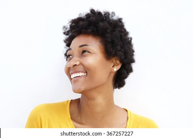 Closeup portrait of happy young african woman looking away against white background