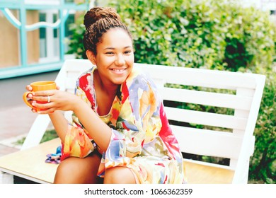 Closeup portrait of happy young black woman drinking coffee