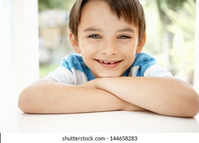 Closeup portrait of happy young boy leaning into window