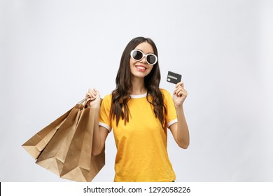 Close-up portrait of happy young brunette woman in sunglasses holding credit card and colorful shopping bags, looking at camera, isolated on white background