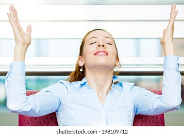 Closeup portrait happy young business woman in blue shirt looking upwards, hands raised in air relaxing on red couch, armchair isolated city background. Corporate life style. Stress relief techniques