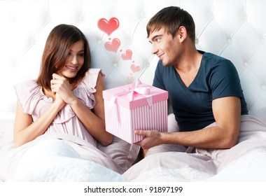 Closeup portrait of a happy young couple relaxing on the bed. Man making a gift to his girlfriend. Saint Valentine`s day concept. Graphic heart.
