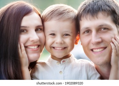 Close-up portrait of a happy young family. Mom, dad and little son look at the camera and smile. The faces of Caucasian parents and their child.