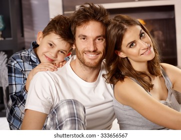 Closeup portrait of happy young family with little boy, smiling, looking at camera.