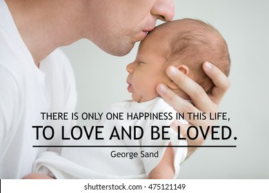"Close-up portrait of happy young father hugging and kissing his sweet adorable newborn child. Motivational phrase ""There is only one happiness in this life, to love and be loved"". George Sand"
