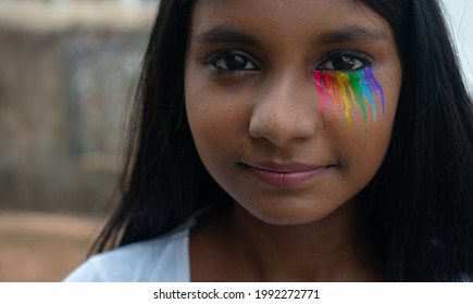 Close-up portrait of a happy young gender fluid girl with rainbow tears staring at the camera representing LGBTQ community