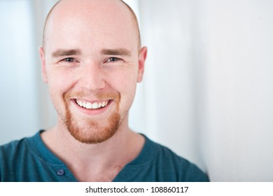 Closeup portrait of happy young man smiling isolated on bright background with copyspace