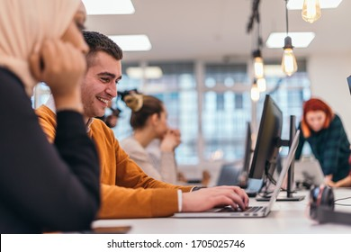 Close-up portrait of a happy young man sitting in an office next to his colleagues and working on his laptop.