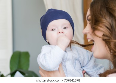 Close-up portrait of happy young mother hugging and kissing his sweet adorable child. Indoors shot, concept image.