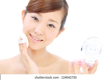 Closeup portrait of a happy young woman applying make up on her face