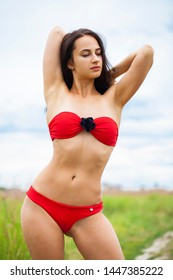 Closeup portrait of a happy young woman in red bikini, summer outdoors