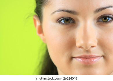 Closeup portrait of a happy young woman over green