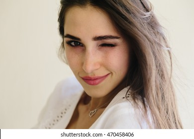 Closeup portrait of a happy young woman smiling and winking. Perfect skin with freckles, wavy healthy hair. Isolated on light yellow wall. Copy space text.