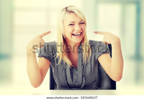 Closeup portrait of a happy young woman smiling sitting with hand on desk