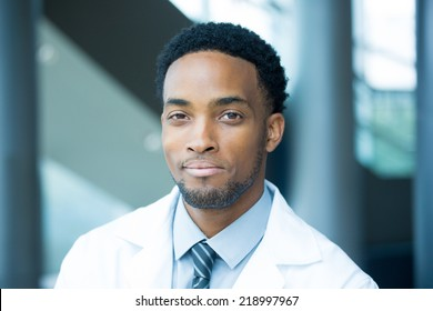Closeup portrait head shot of friendly, smiling confident male healthcare professional with a white coat, isolated hospital clinic background.