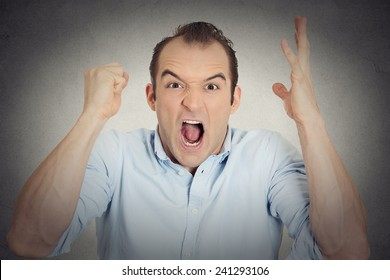 Closeup portrait headshot angry upset young man worker mad employee funny looking businessman fist in air open mouth yelling isolated grey wall background. Negative emotion facial expression reaction