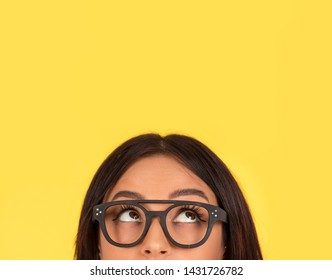 closeup portrait headshot cropped face above lips of cute happy woman in glasses looking up isolated on yellow studio wall background with copy space above head. Human face expressions, emotions