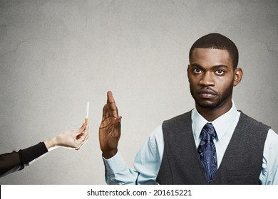 Closeup portrait, headshot handsome young business man says no to cigarette offered by person, stop hand gesture, isolated black, grey background. Healthy life choices. Human face expression, reaction