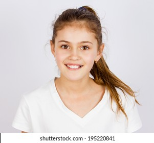 Closeup portrait, headshot happy, smiling, excited, funny looking little girl, isolated grey background. Positive human emotions, facial expressions, attitude, life perception, reaction
