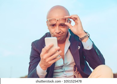 Closeup portrait headshot middle aged man with glasses skeptical looking to the cell phone screen sitting outdoors blue sky on background. Negative face expression human emotion reaction body language