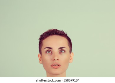 closeup portrait headshot one funny woman boy alike looking up green wall background with copy space for text above head. Human face expression, emotions, feelings, body language