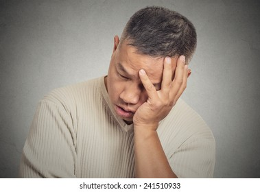 Closeup portrait headshot sad bothered stressed middle aged man holding head with hand really depressed about something isolated grey wall background. Negative human emotion facial expression feeling