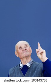 Closeup portrait, headshot serious, concerned, senior mature man looking, pointing index finger up, isolated blue background. Human emotions, facial expressions, feelings, signs, reaction, perception