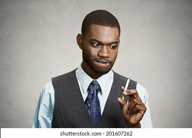 Closeup portrait, headshot, young handsome business man, corporate executive, funny looking guy, craving cigarette, tobacco, isolated black grey background. Bad, dangerous human health habits concept