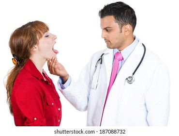 Closeup portrait, health care professional performing oral, throat, neck physical exam holding face looking inside mouth of patient woman standing saying ahhhh, isolated, white background.