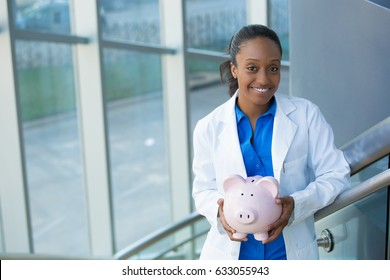 Closeup portrait, healthcare professional holding piggy bank isolated indoors clinic hospital background.  Health savings financial concept