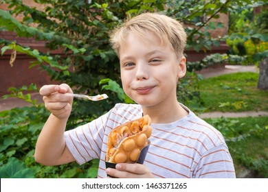 Closeup portrait of healthy happy white kid eating tasty sweets outdoors in street. Child holds big wafle cone filled with ice-cream, marshmallow and other sweets. Horizontal color photography.