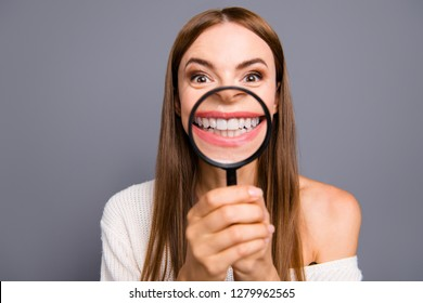 Close-up portrait of her she nice crazy attractive cheerful brown-haired lady showing perfect healthy teeth denture through loup isolated over gray pastel background