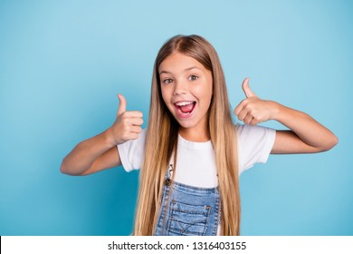 Close-up portrait of her she nice cute adorable lovely sweet attractive cheerful cheery straight-haired blonde pre-teen girl opened mouth showing thumbup isolated on blue pastel background
