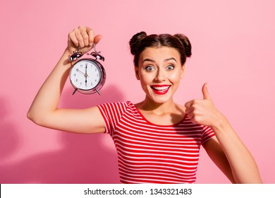 Close-up portrait of her she nice cute charming winsome attractive glamorous cheerful girl wearing striped t-shirt holding in hand showing clock thumbup hour isolated over pink pastel background