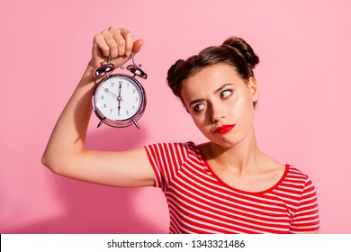 Close-up portrait of her she nice cute charming attractive glamorous sad teen girl wearing striped t-shirt holding in hand showing clock boring hour isolated over pink pastel background