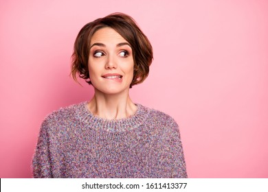Close-up portrait of her she nice attractive lovely lovable pretty cute charming girlish funny unsure brown-haired girl biting lip looking aside isolated over pink pastel color background