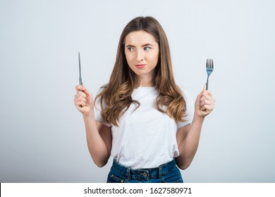 Close-up portrait of her she nice attractive lovely winsome girl holding in hands fork knife choosing healthy organic dieting day daily menu isolated over light white color background